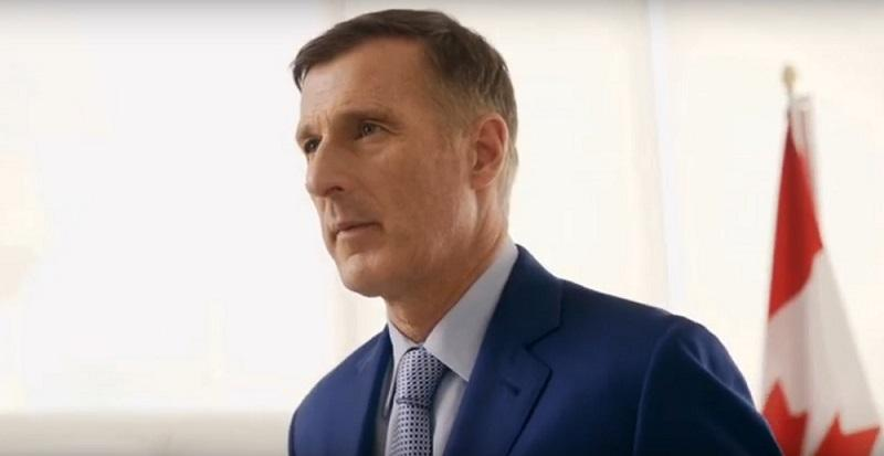 Image of Maxime Bernier in a blue suit with a glimpse of Canadian flag in the background