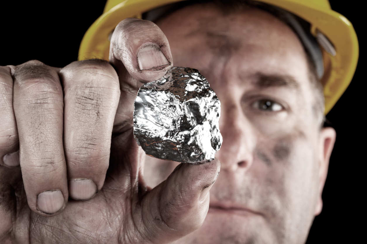 Image of a miner holding up a large gold nugget.