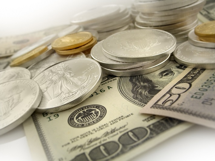 Silver coins loosely stacked on top of US paper money.