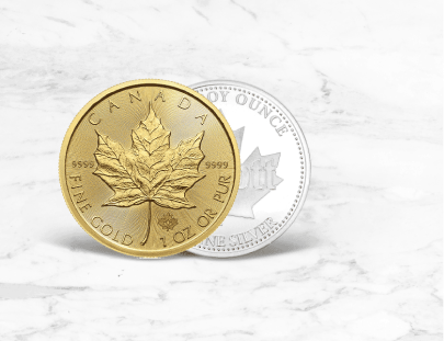 A gold coin on overlapping a silver coin on a marble background